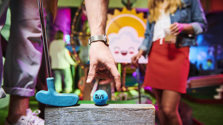 A blue golf ball is placed on a wooden block, with a blue golf club next to it, ready to strike
