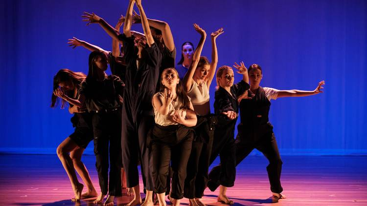 A group of performers pose in different positions on a blue-lit stage