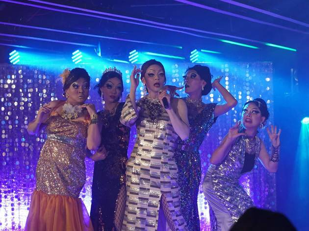 Five asian drag queens performing on a stage backed with blue lighting