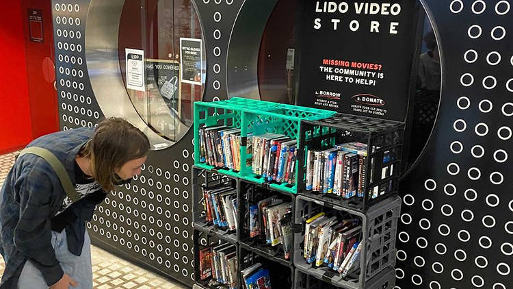 A man browsing the DVD and VHS library outside of Lido Cinemas.