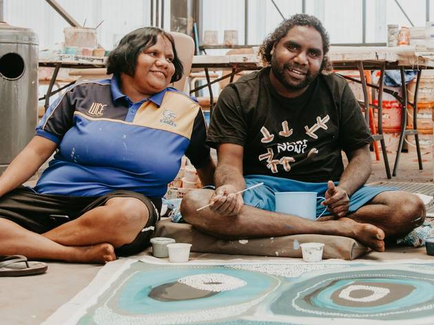 Western Desert artists Corban Clause Williams and Judith Anya Samson sit on a studio floor painting together