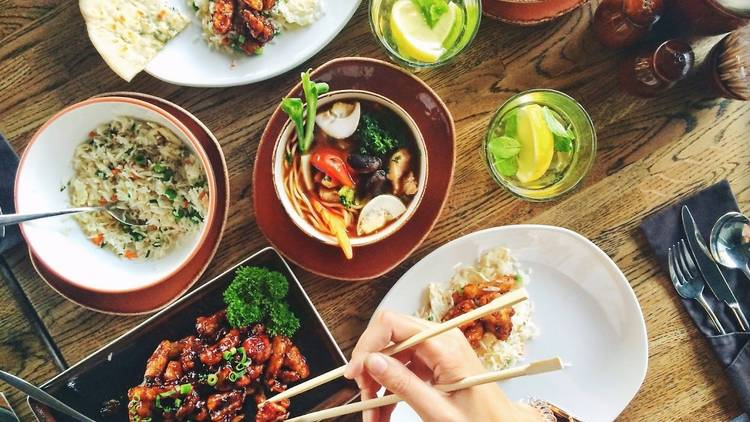 A table of food and a person using chopsticks