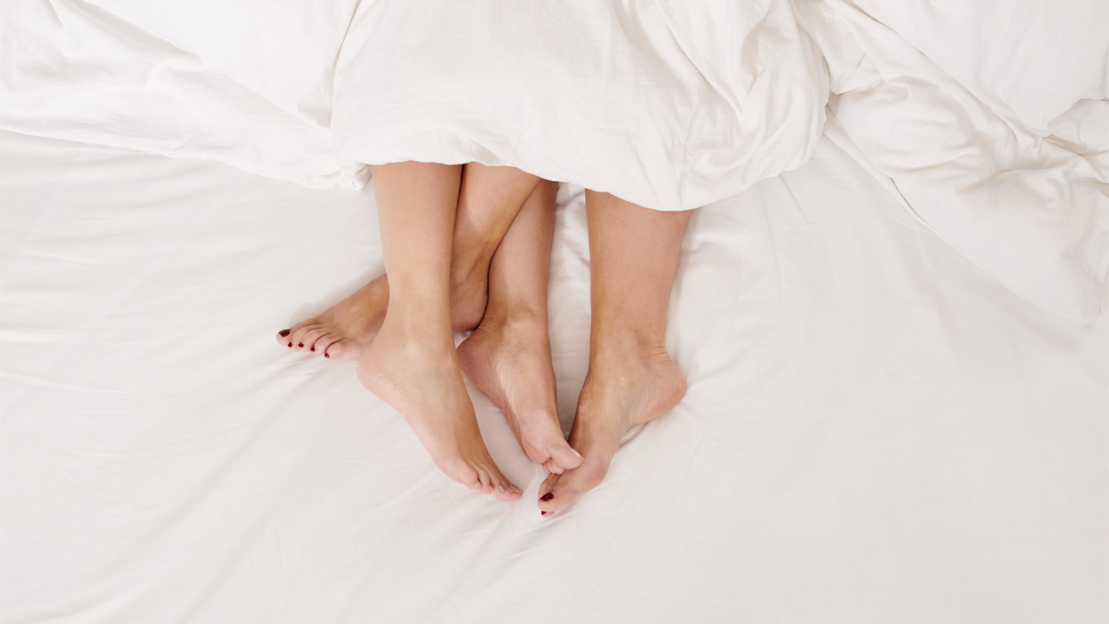 Two sets of feet are intertwined and poking out from a blanket on white sheets.