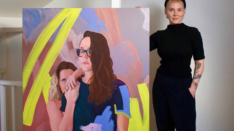 A womany stands next to a colourful painting that's almost as tall as she is