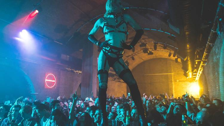 A person in leather harness stands on a speaker above a crowd dancing