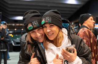 Two women wearing sleep at the g beanies.