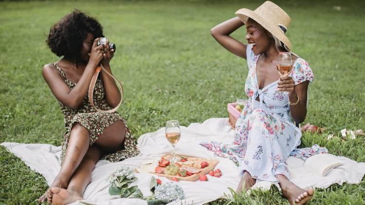 Two women having a picnic outdoors.