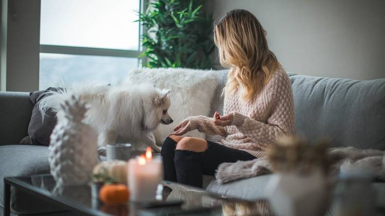 Woman on couch with dog and candle