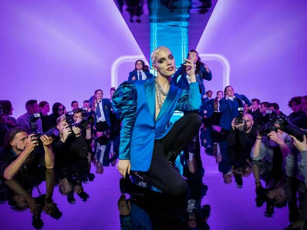 A close up of Max Harwood wearing a bright blue blazer on a purple-lit catwalk in Everybody's Talking About Jamie