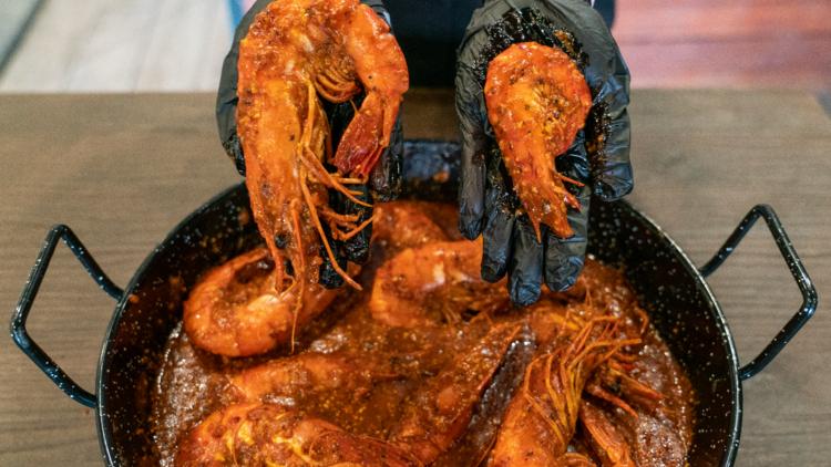 a black bowl of cajun style prawns