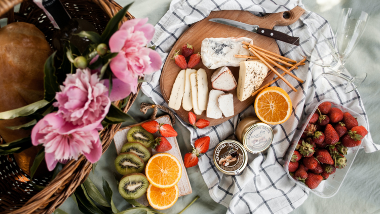 A flat lay of a picnic with cheeses, fresh fruit, a gingham rug and pink flowers