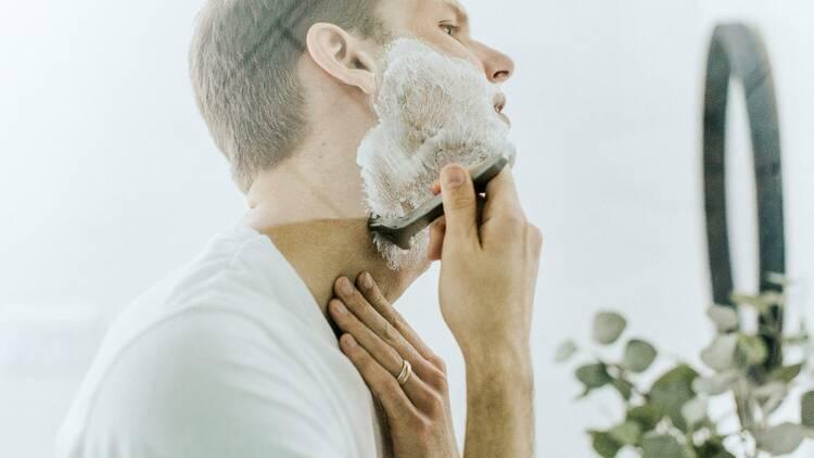 A man shaving his face.