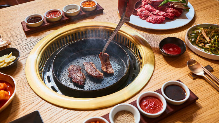 A rib-eye Korean barbecue spread at Daedo Sikdang, including four house sauces and green onion salad.