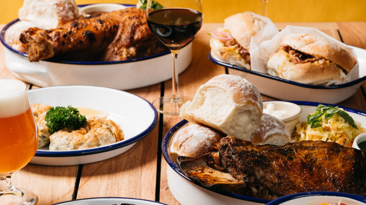 A wooden table with white metal plates of roasted lamb, bread rolls, french onion dip and glasses of wine and beer with a yellow ochre background