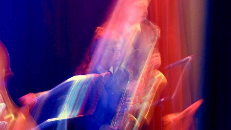 Musician Flora carbon playing the saxophone with a funky pink and blue filter on the image