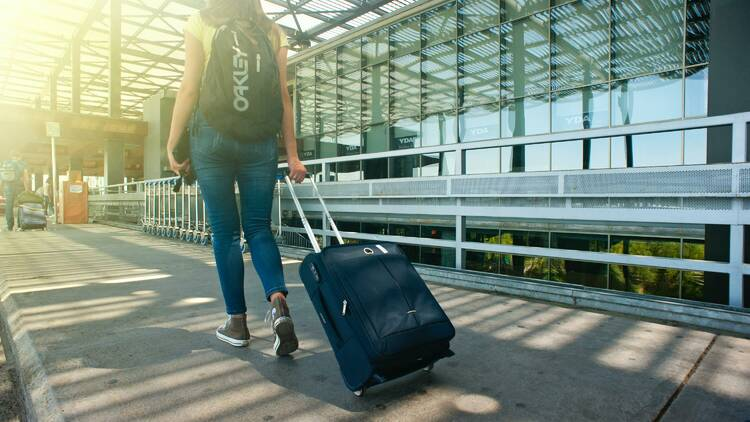 Woman wearing a backpack pulling a suitcase through an airport