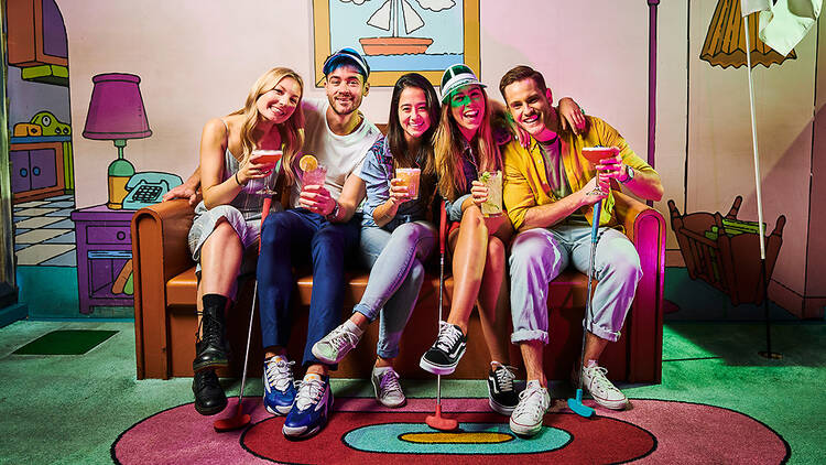 Five friends holding golf clubs and colourful cocktails grin and embrace as they sit on the famous couch tableau from The Simpsons.