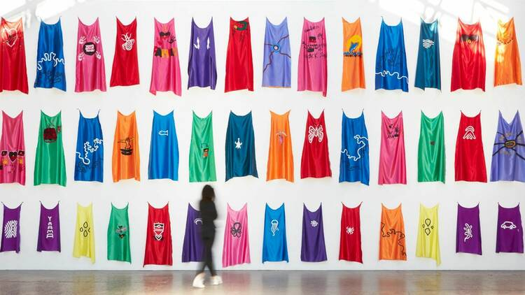 a woman drese din black jeans and top looks at a white gallery wall at Carriageworks covered in colourful superhero capes designed by First Nations children