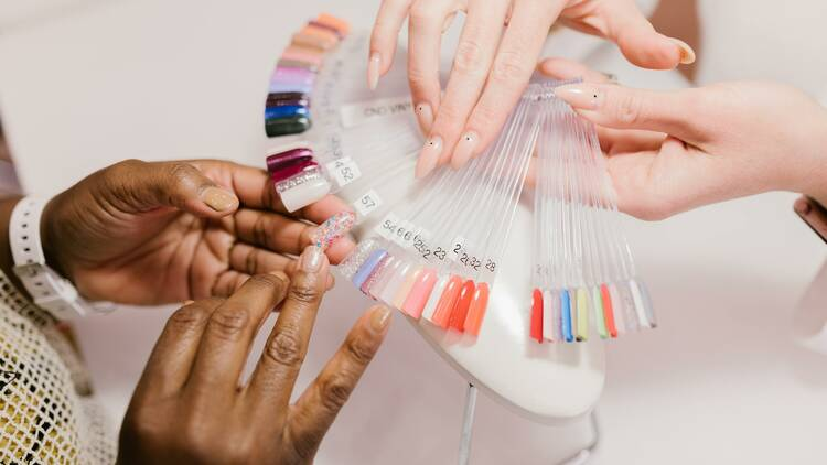 Someone picking a colour for their manicure from a set of samples.
