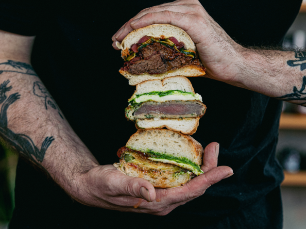 A man holding three halved sandwiche that have meat and schnitzel.