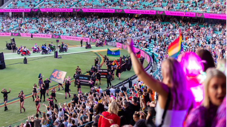 A crowd in the SCG stadium cheers on the Mardi Gras parade.