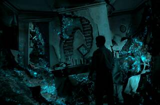 A man in shadow exlores what appears to be the ruined remains of a house bathed in deep blue light