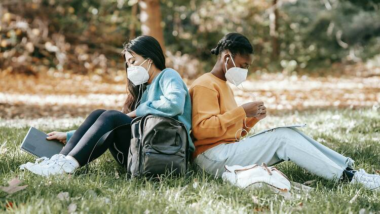 Two women sitting back to back in a park, both wearing face masks