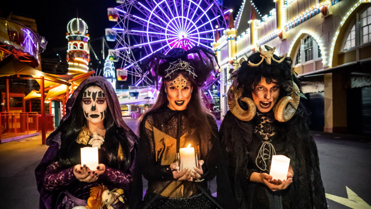 Three witches in spooky garb hold candles and stand in the middle of Luna Park with the ferris wheel behind them