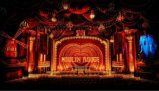 The Regent Theatre transformed into the Moulin Rouge, with a giant windmill and blue elephant on the sides of the stage